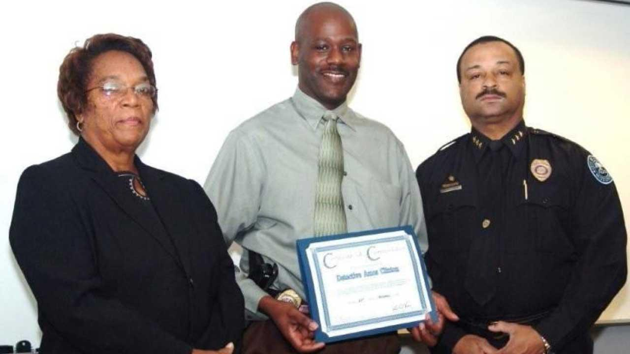 In this 2008 image provided by the Jackson, Miss. Police, Detective Eric Smith, center, flanked by Chief Rebecca Coleman, left, and Assistant Chief Lee Vance accepts the Certificate of Commendation on behalf of Detective Amos Clinton in Jackson, Miss. Authorities say a murder suspect shot Smith inside the Jackson police headquarters and that both the suspect and detective are dead. (AP Photo/Jackson Police)