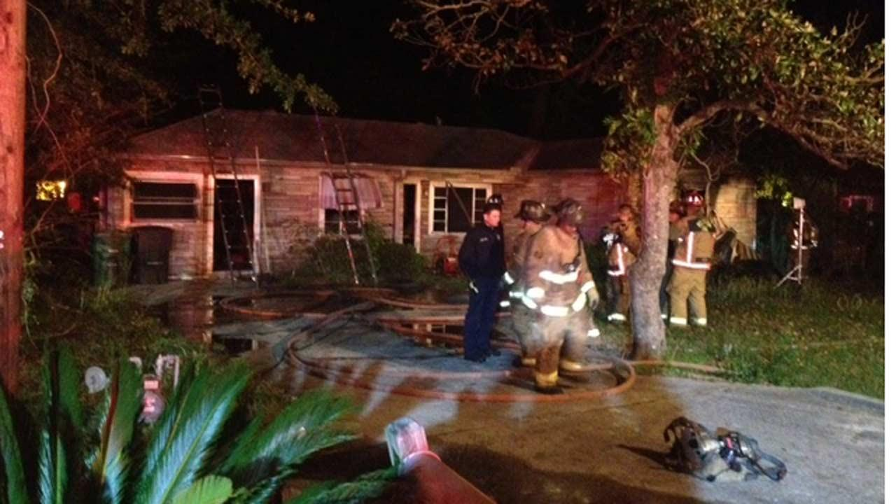 Officials say a Houston firefighter was injured after falling through the roof of this home
