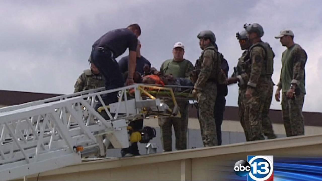 SWAT officers ultimately brought a suspect down from the roof in a gurney