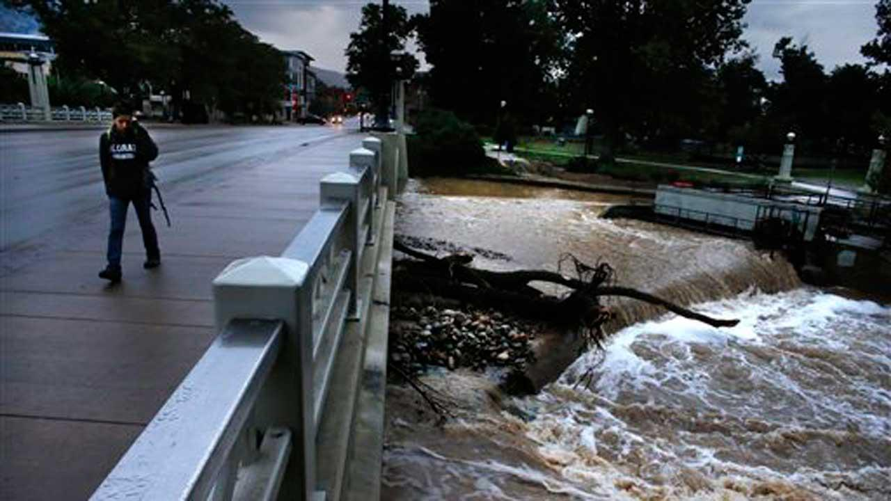 A woman walks past Boulder Creek, whose swollen waters have receded somewhat since the intense rain which had fallen for days has abated over the past two days, in Boulder, Colo., Sunday, Sept. 15, 2013