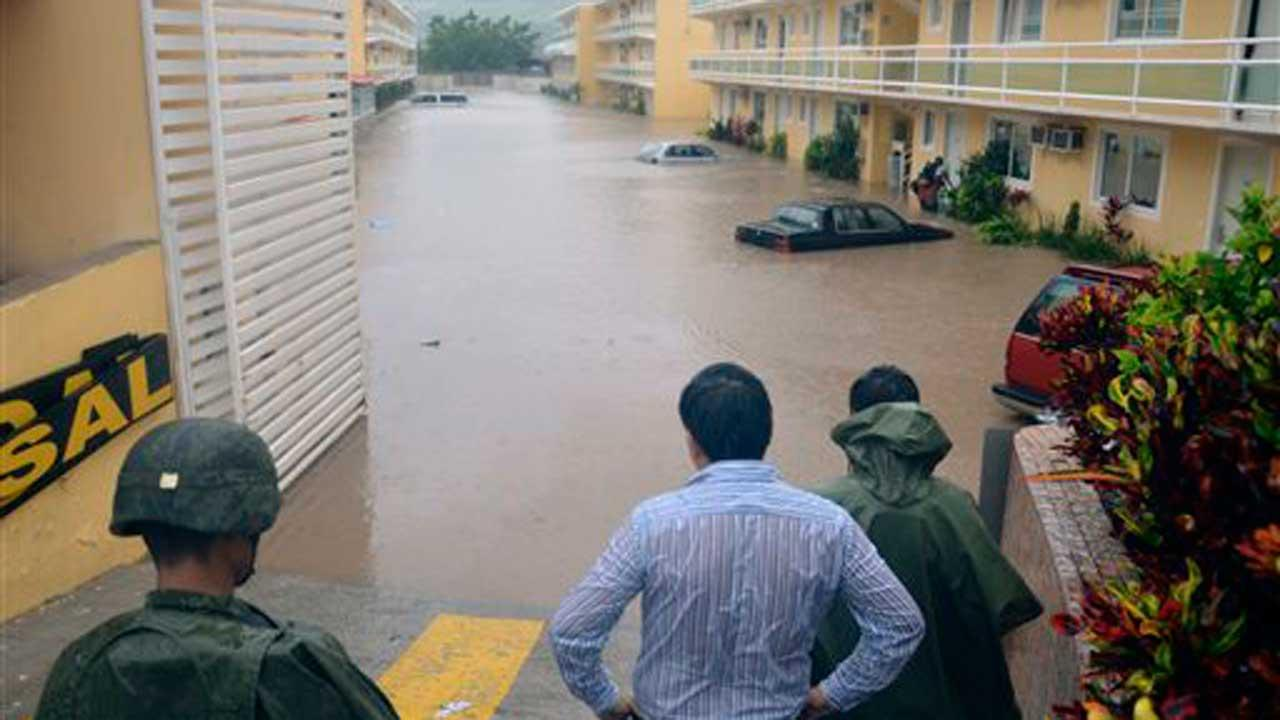 Army soldiers and a civilian look out into a flooded street caused by Tropical Storm Manuel in the city of Chilpancingo, Mexico, Sunday Sept. 15, 2013.