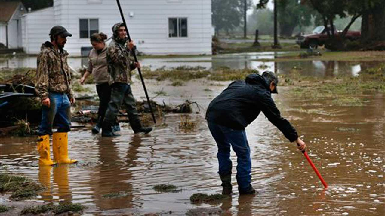Local residents help salvage and clean property in an area inundated after days of flooding, in Hygeine, Colo., Monday Sept. 16, 2013