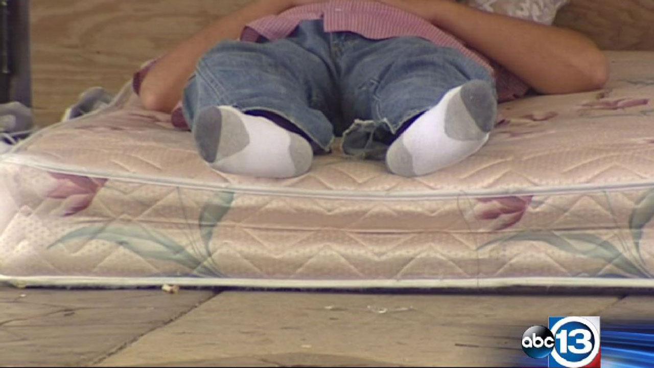 A homeless man lies on a mattress outside an abandoned restaurant in northwest Harris County