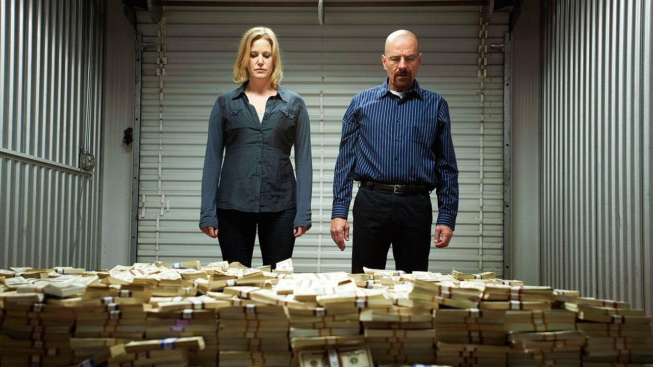 This image released by AMC shows Skyler White, played by Anna Gunn, left, looking over a stash of money with her husband Walter White, played by Bryan Cranston, in season five of Breaking Bad.