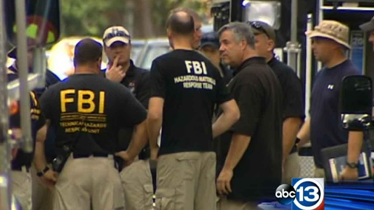 FBI officials gather outside a Memorial-area home in Houston where there were two controlled detonations Saturday