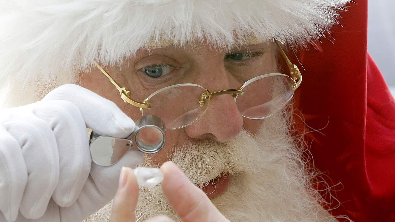 Actor Brady White portrays Santa Claus as he looks at a 25-carat rough Forevermark diamond
