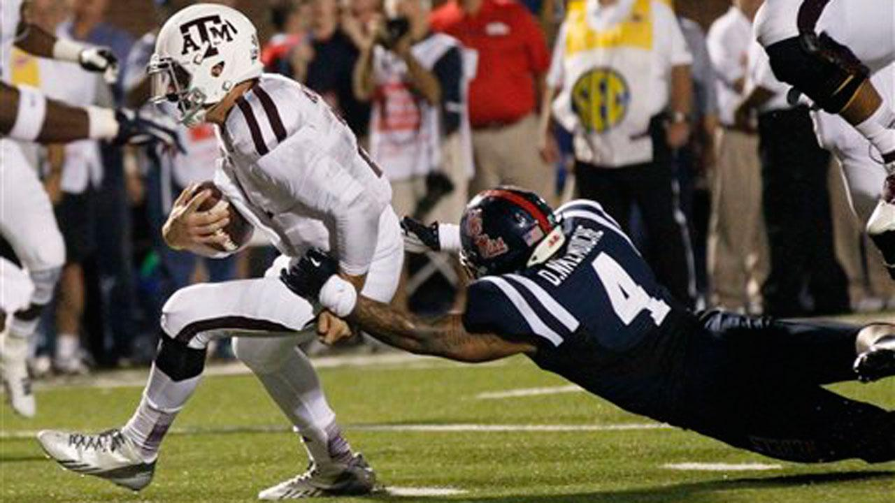 Texas A&M quarterback Johnny Manziel (2) drags Mississippi linebacker Denzel Nkemdiche (4) as he breaks free for a five-yard touchdown run in the second half of their NCAA college football game on Oct. 12, 2013