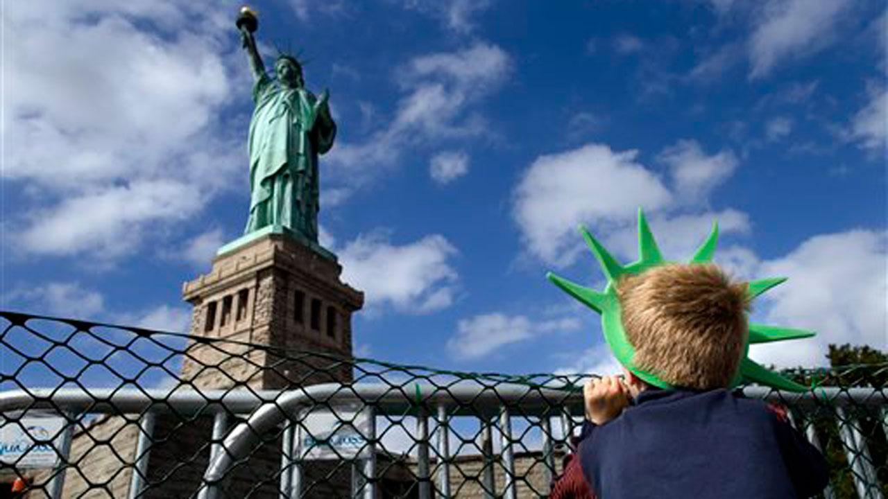 Jackson Blendowski, 6, of New Hampshire, peers up at the Statue of Liberty in New York Harbor, Sunday, Oct. 13, 2013, in New York