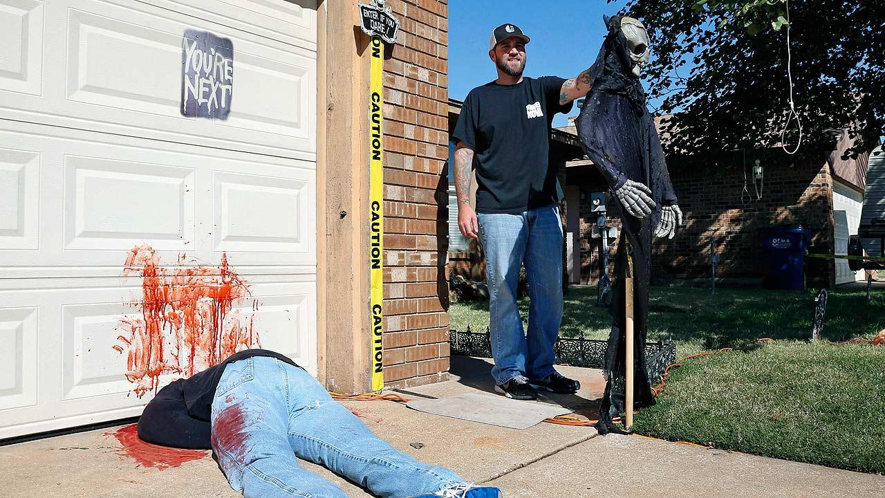 Johnnie Mullins poses with his controversial Halloween display featuring headless dummies dressed in his work clothes at his home