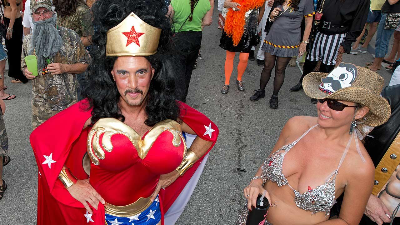 In this Friday, Oct. 25, 2013, Sam Trophia, left, poses in his Wonder Woman costume during the Fantasy Fest Masquerade March in Key West