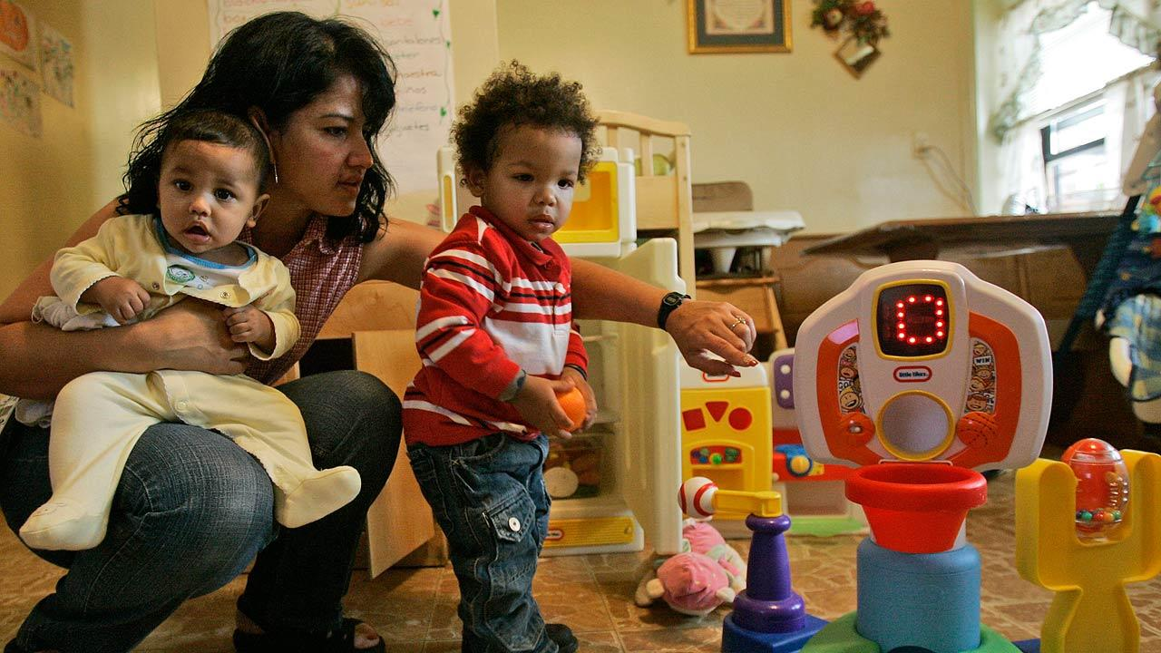 Home-based child care worker Jennie Rivera holds 5-month-old Erick while helping Christian, 1, at her apartment in New York.