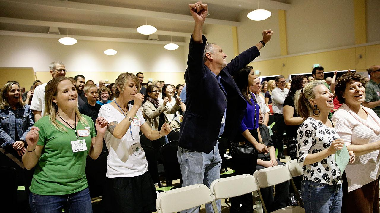 Attendees sing a song at the Sunday Assembly, a godless congregation
