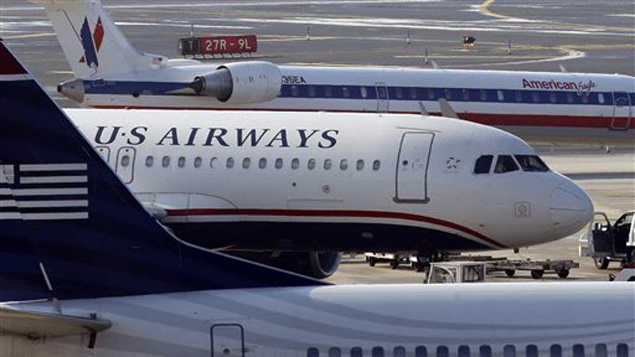 American Airlines and US Airways jets park at gate at the Philadelphia International Airport, Thursday, Feb. 14, 2013