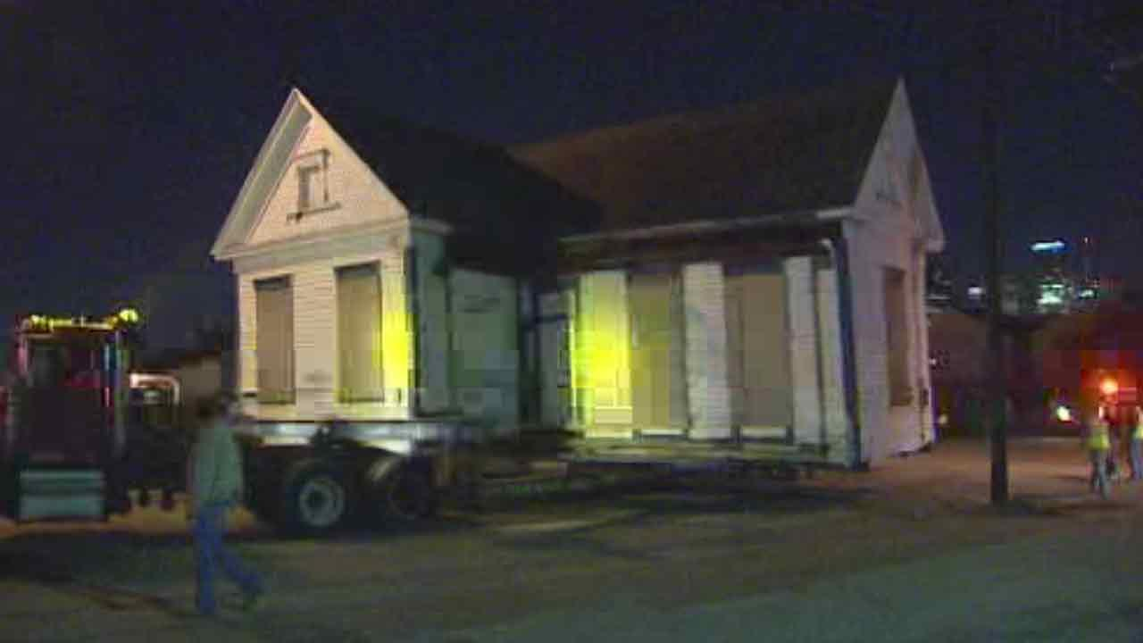 One of six houses is moved about half a mile to its new home where it will be restored
