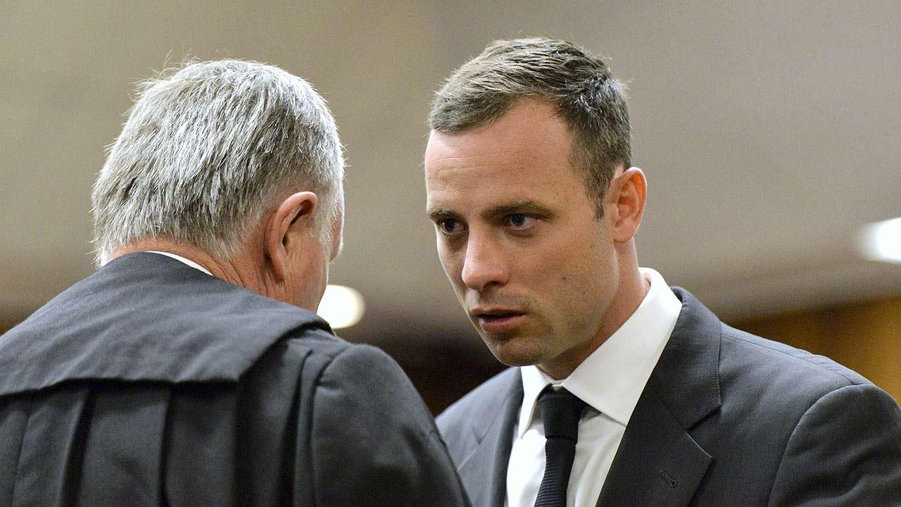 Oscar Pistorius, right, speaks with his lawyer Barry Roux