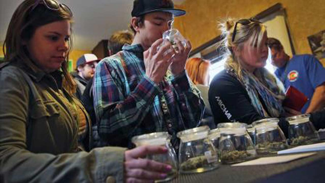 Customers, left to right, Alli Bertucci, Patrick Bean, and Ali Regan shop for marijuana inside the retail store at 3D Cannabis Center, in Denver, Friday Feb. 14, 2014. (AP Photo / Brennan Linsley)
