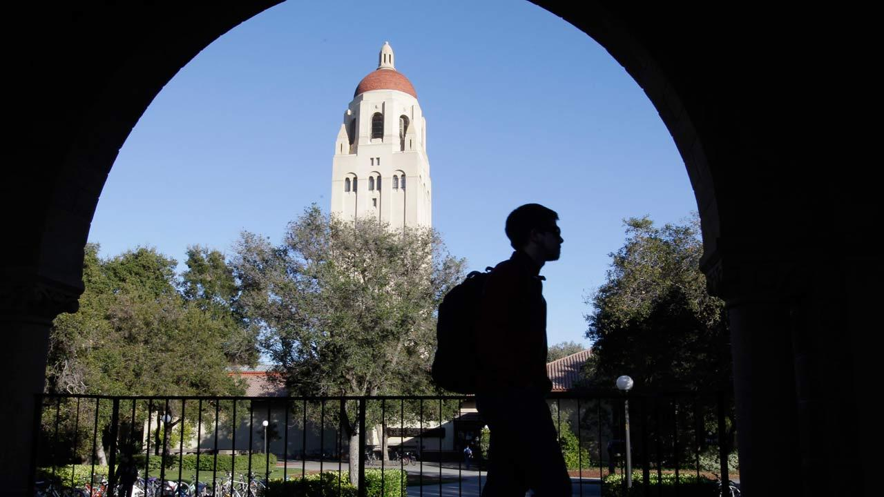In this Feb. 15, 2012 file photo, a Stanford University student walks in front of Hoover Tower on the Stanford University campus in Palo Alto, Calif. (AP Photo/Paul Sakuma, File)