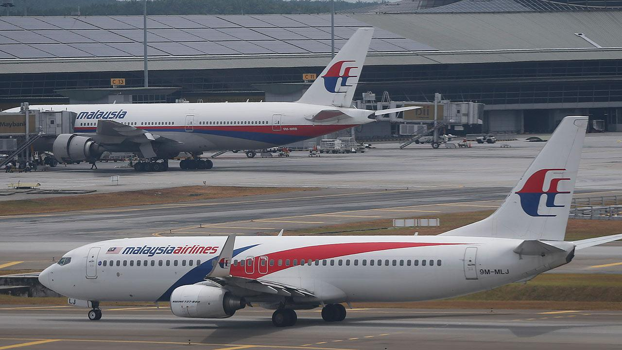 A Malaysia Airline Boeing 737-800 plane taxis by main terminal at Kuala Lumpur International Airport