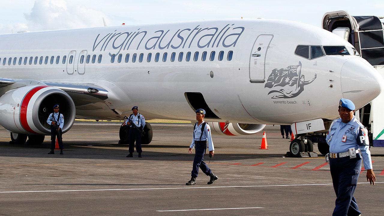 Indonesian air force personnel stand guard near a Virgin Australia airplane in Bali, Indonesia