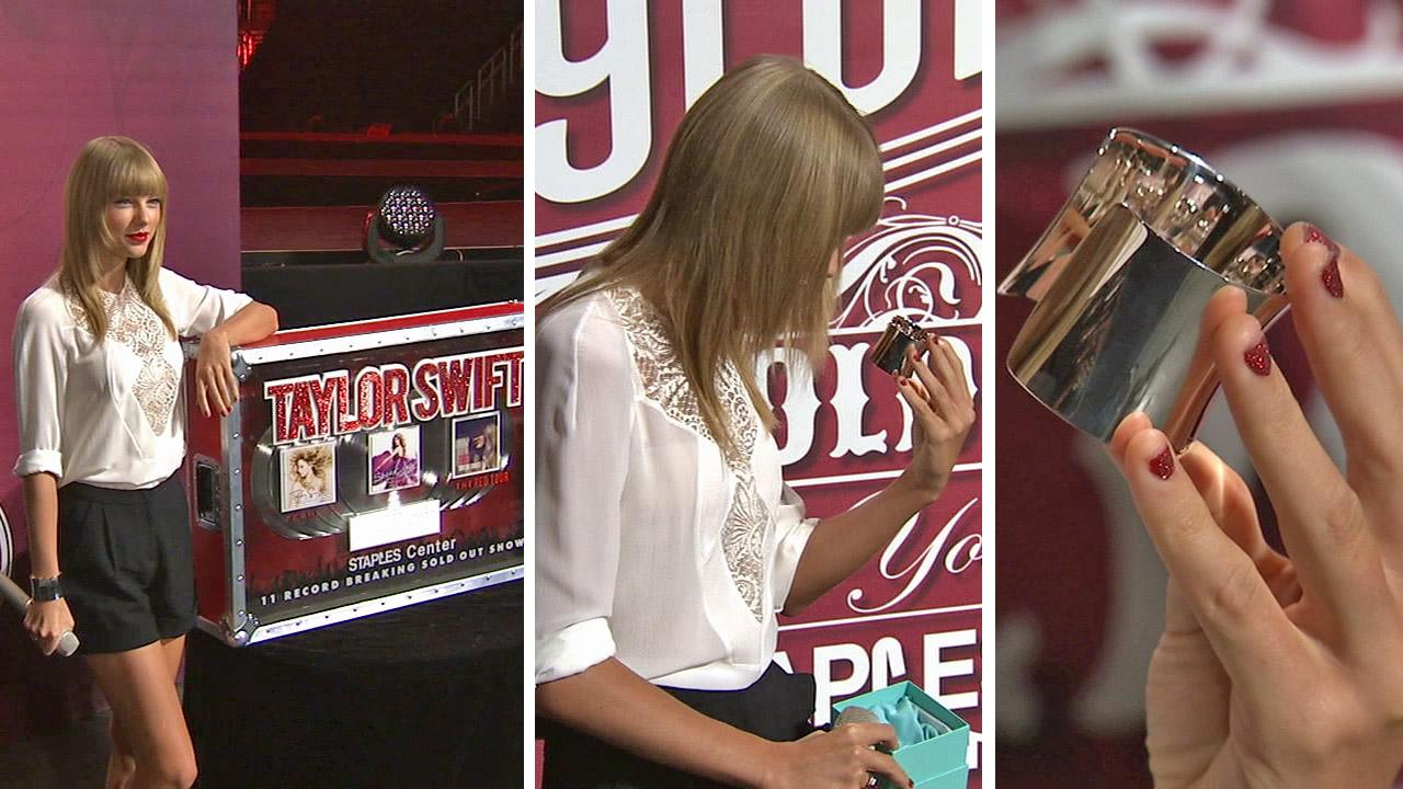 Taylor Swift is presented with a Tiffany cuff bracelet from Los Angeles Staples Center Senior Vice President and General Manager Lee Zeidman for setting the record for having the most sold-out shows for a solo artist, on Aug. 20, 2013.