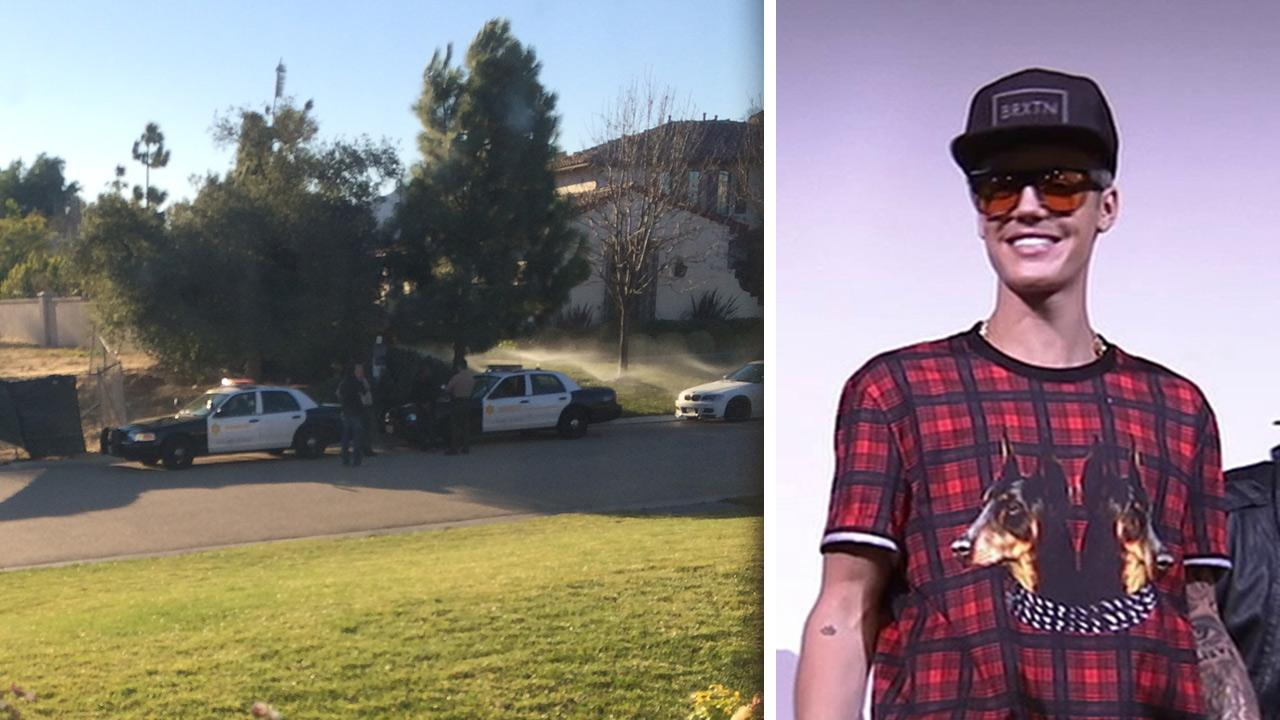 Police squad cars are seen near Justin Biebers L.A. home on Jan. 14, 2014. He was served with a search warrant amid a probe into an incident, in which he is accused of egging a neighbor. / Bieber appears at a Believe screening on Dec. 16, 2013.