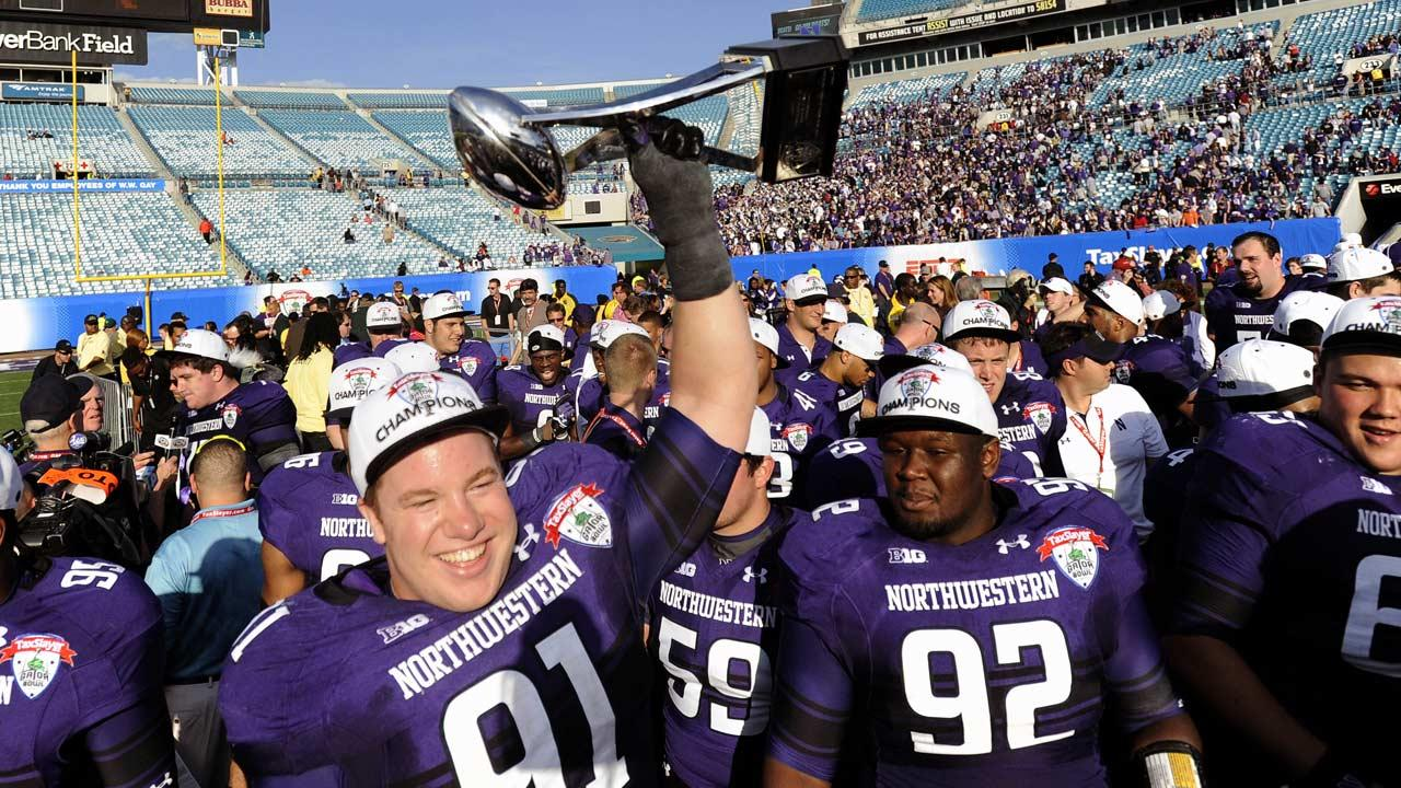 Northwestern defensive lineman Brian Arnfelt (91) holds the trophy along with his teammate Will Hampton (92) after their 34-20 win over Mississippi State in the Gator Bowl NCAA college football game, Tuesday, Jan. 1, 2013 in Jacksonville, Fla.  (AP Photo/Stephen Morton)