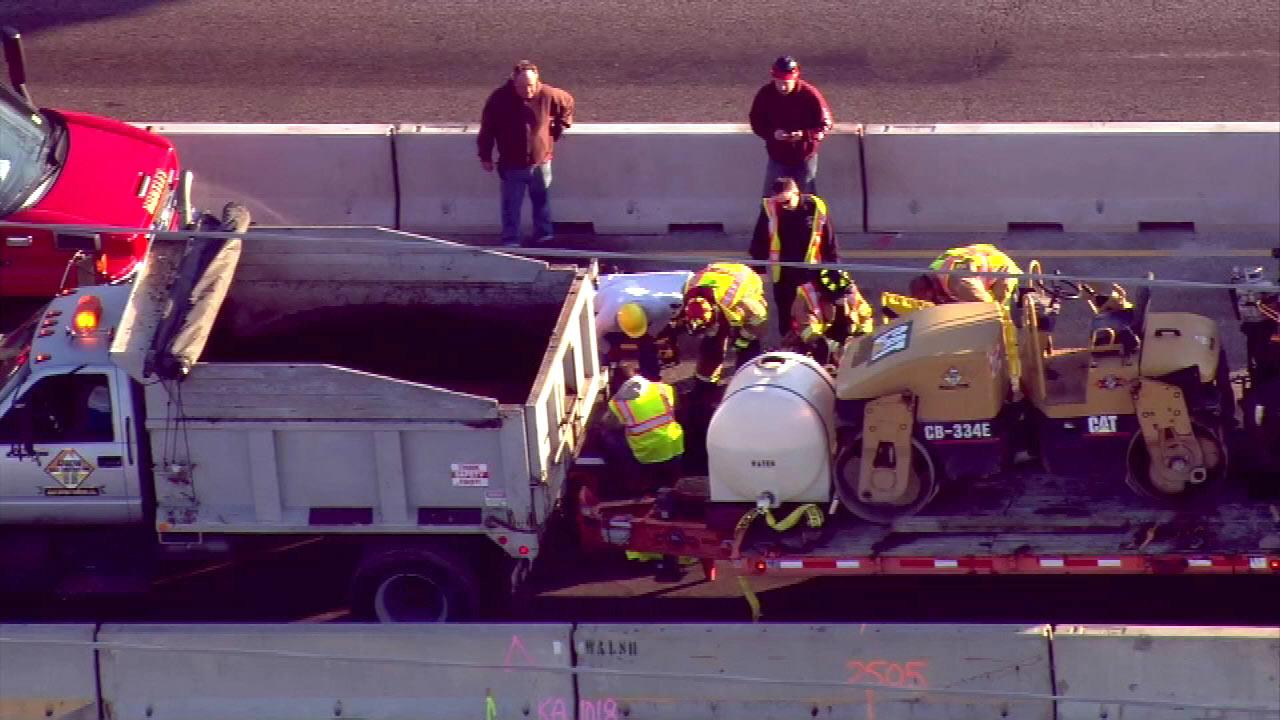 A piece of paving equipment slid off the side of a flatbed truck, pinning the workers legs, according to unconfirmed reports.