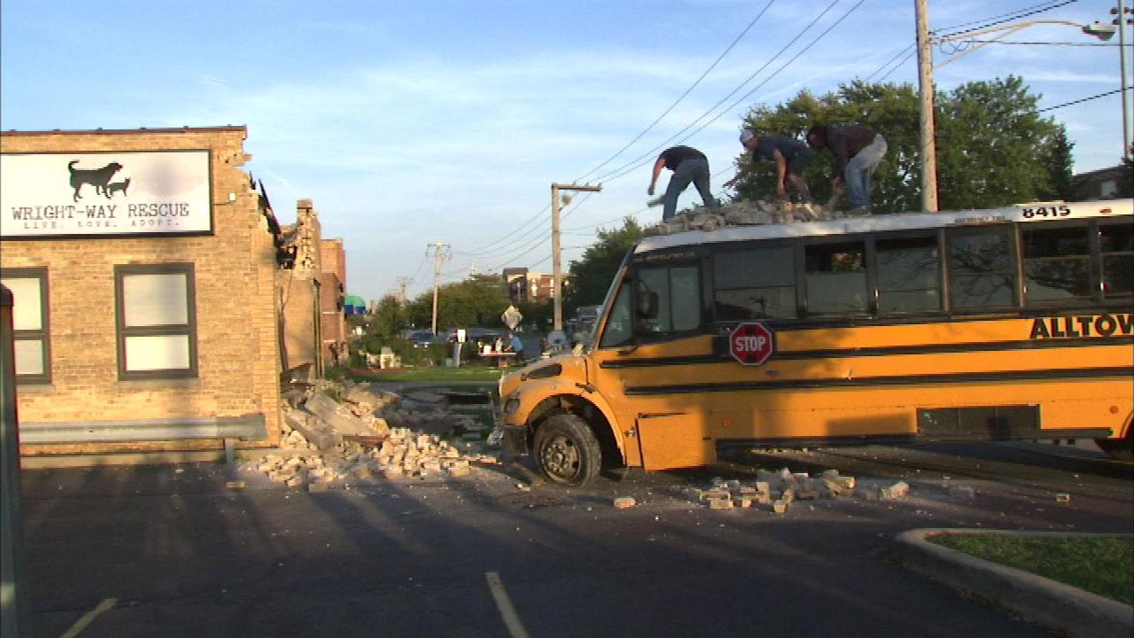 Workers remove debris from a school bus that crashed into the front of an animal rescue center in the 7100-block of West Touhy in north suburban Niles Wednesday afternoon.