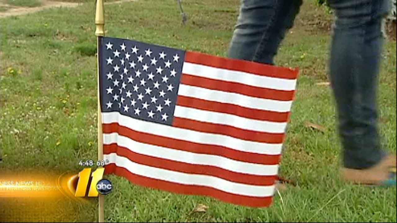 Volunteers place flags for Memorial Day