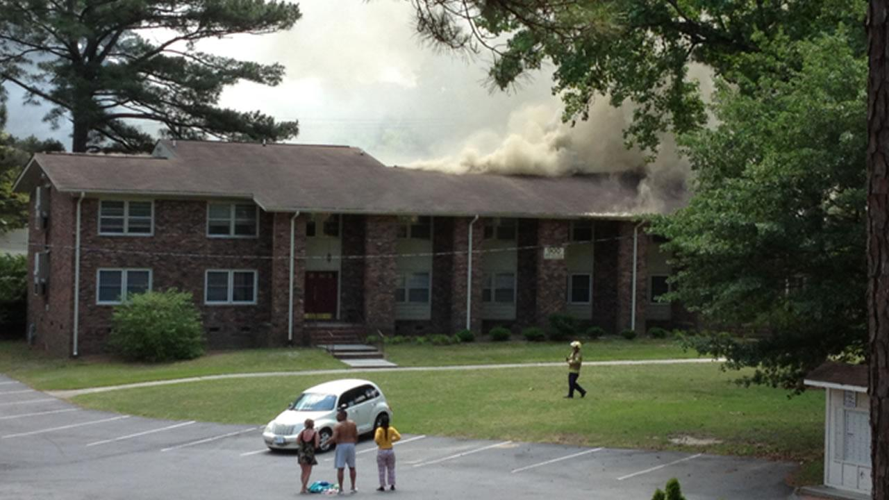 Smoke comes from the roof of a building at the Carriage Hill Apartments in Fayetteville.