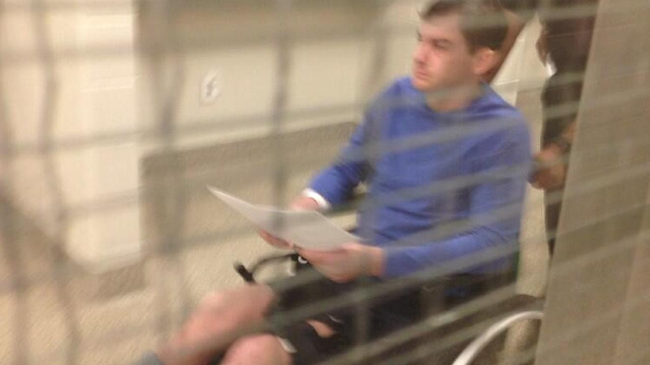 Ray Rouse IV is taken to see a magistrate in a wheelchair.