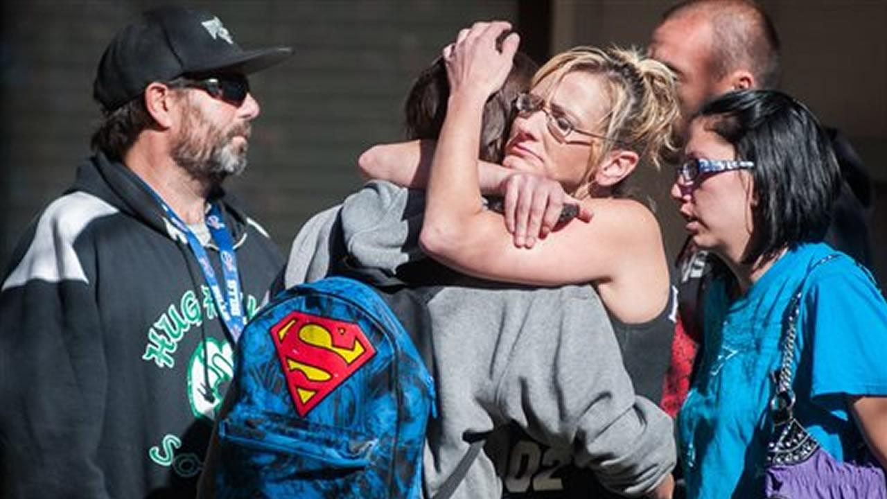 A Sparks Middle School student, back to camera, cries with family members after being released from Agnes Risley Elementary School Monday Oct. 21, 2013, in Sparks Nev.
