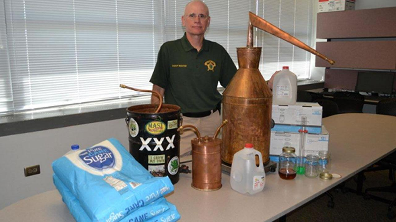 Chatham County Sheriff Richard H. Webster with a confiscated liquor still.