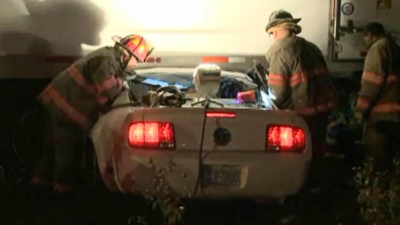 Firefighters rescue a man from his car.