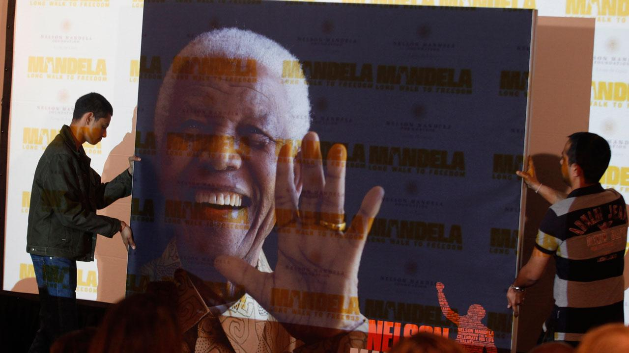 A giant poster of Nelson Mandela is moved to center stage at a news conference held on the eve of the South African premier of the film Mandela - Long Walk To Freedom, in Johannesburg, Saturday Nov. 2, 2013.