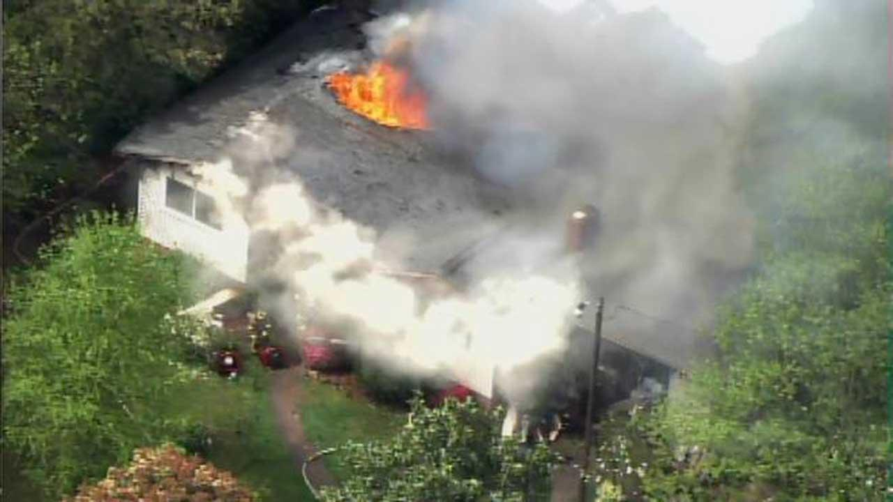 Flames seen shooting through the roof of a home on Barclay Drive in Raleigh Thursday morning.