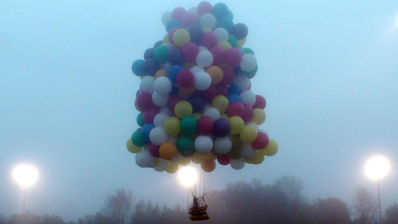 In this photo provided by Mark McBreairty, a balloon cluster carrying Jonathan Trappe lifts off from Caribou, Maine, Thursday, Sept. 12, 2013.